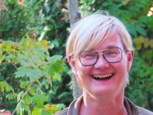 Foto von Monika Stiebing. Sie trägt eine Brille, lächelt und hat kurze, hellblonde Haare.