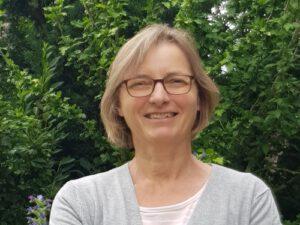 Foto von Antje Tinkloh. Sie trägt eine Brille, lächelt und hat kinnlanges dunkelblondes Haar.